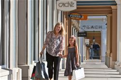 People walking near Coach, J. Crew, Fossil stores at a shopping center.